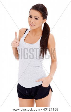 Sporty woman showing thumb up gesture while isolated on white