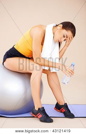 Young beautiful Woman sitting on fitness ball with towel around her neck