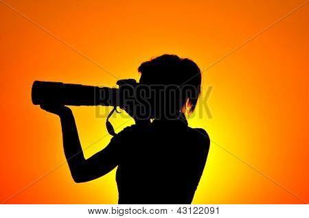 Photographer silhouette shooting sea outdoors at sunset background