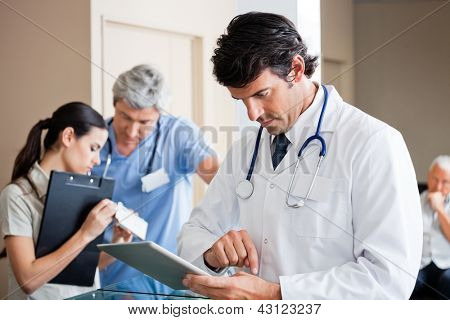Mid adult male doctor using digital tablet with people in background