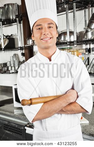 Portrait of happy chef standing with arms crossed in restaurant kitchen