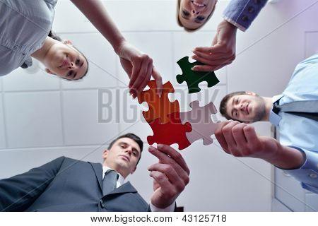 Grupo de empresarios, armar rompecabezas y concepto de apoyo y ayuda de equipo representan