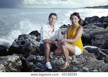 Young couple posing by the sea