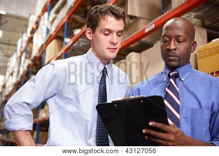 Two Businessmen With Clipboard In Warehouse