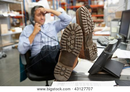 Businessman Putting Feet Up On Desk In Warehouse