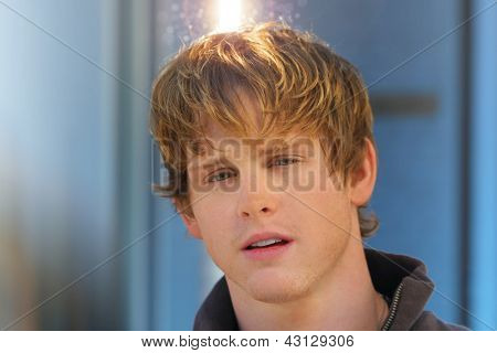 Young male model with flare light halo above and behind his head  with copy space