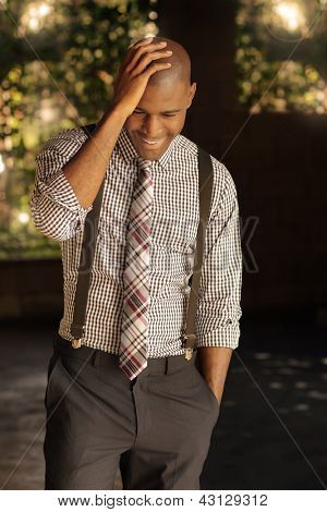Sexy smart modern young businessman with nice smile looking down and hand on head