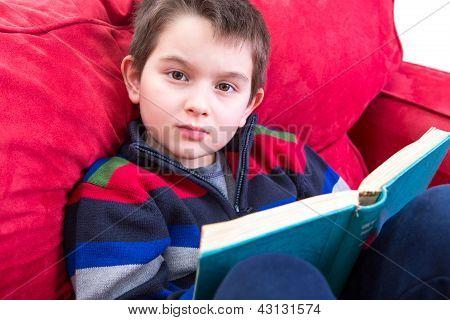 Kid Reading Book On The Couch