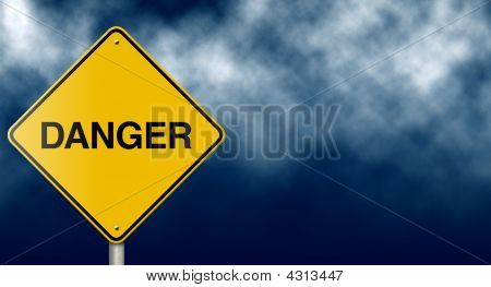 Danger Road Sign On Stormy Sky