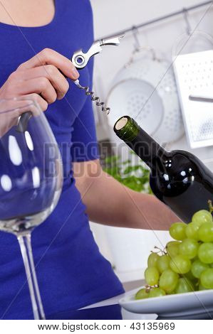 Young Woman Opening A Bottle Of Red Wine In Her Kitchen