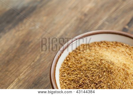 small ceramic bowl of unrefined coconut palm sugar against an out of focus wood background - copy space