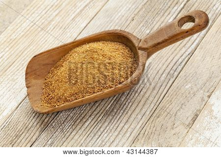 a wooden rustic scoop of unrefined coconut palm sugar against a white painted grunge wood background