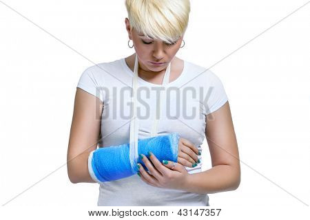 Young woman holding painful arm in blue cast on a white background