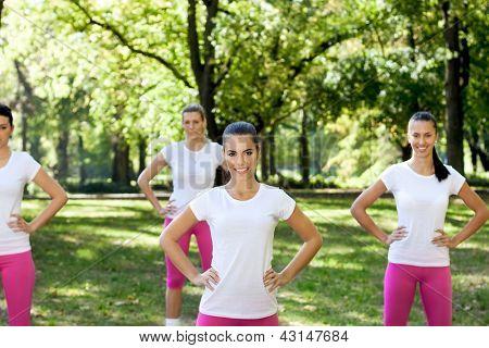 Grupo Desportivo mulher exercitar no parque, sorrindo e olhando na câmera