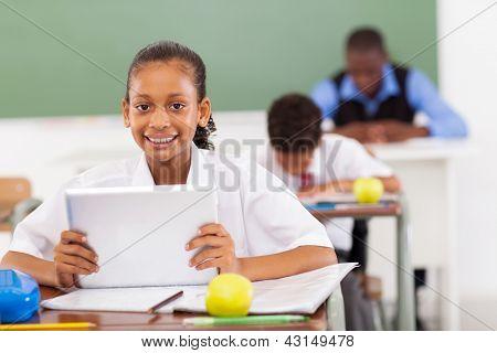primary schoolgirl using a tablet computer in classroom