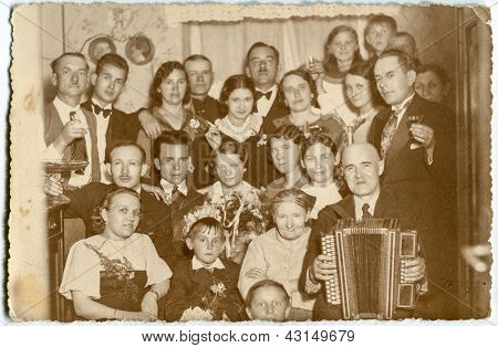 LODZ, POLAND - CIRCA FORTIES: a big unidentified three-generation family poses for a photo during a family event (one of man with an accordion) in forties