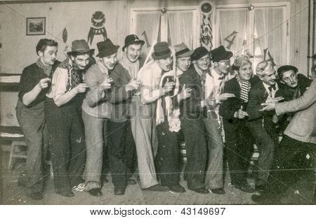 LODZ, POLAND - DECEMBER 31: a group of young unidentified men has fun, dances and drinks alcohol at New Year Eve event on December 31, 1943 in Lodz, Poland