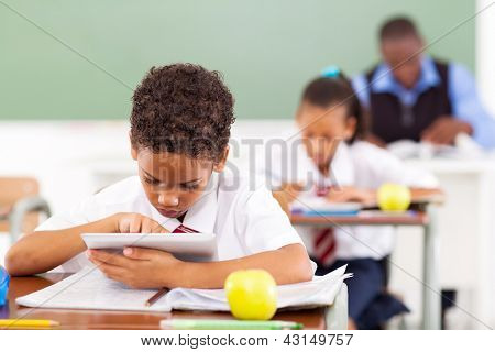 cute elementary schoolboy using a tablet computer in classroom