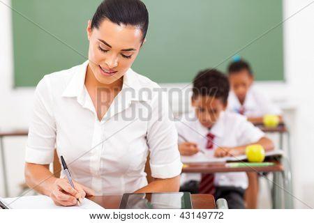 Profesor de la escuela femenina elegante preparar lecciones en el aula