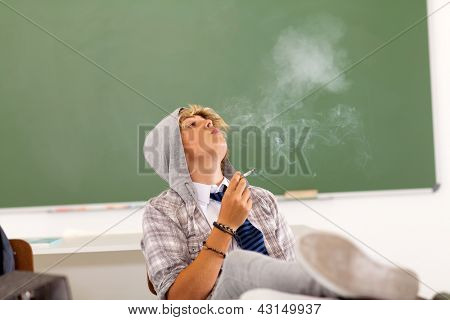 bad high school teen student smoking in classroom