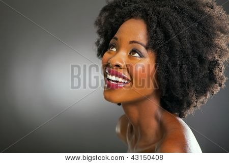 pretty black woman looking up on dark background