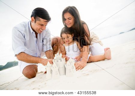 Happy family at the beach making sand castles
