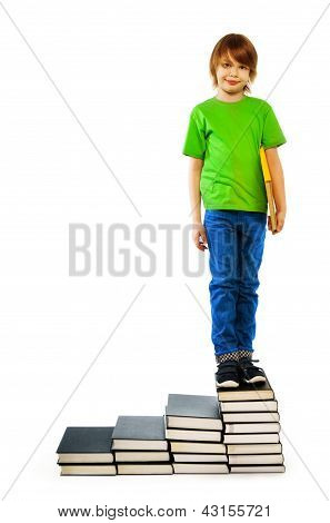 Boy Standing On Stairs Of Books