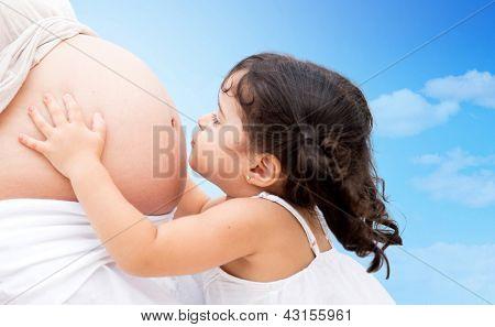 Cute litte girl kissing mums belly outdoors