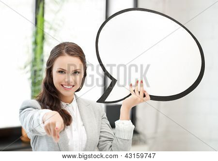 smiling businesswoman with blank text bubble pointing at you