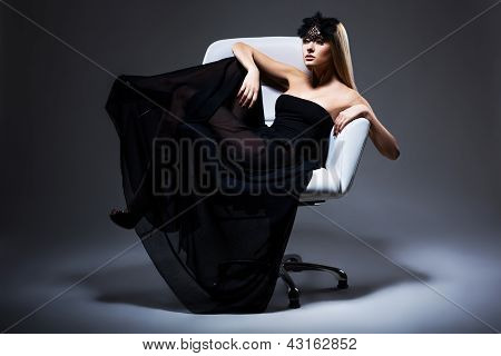 Enjoyment. Classy Elegant Woman Blonde Relaxing In Chair. Black Dress And Mask With Feathers