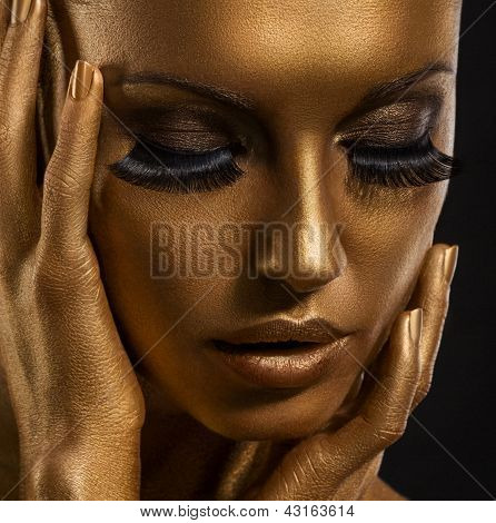Gilt. Golden Woman's Face Closeup. Futuristic Giled Make-up. Painted Skin