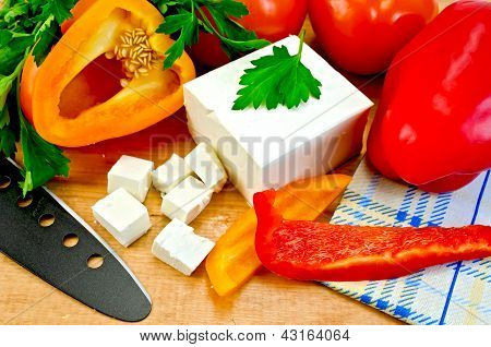 Feta cheese on the board with vegetables and herbs
