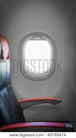 Passenger seat in plane with window aside.