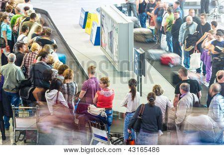 Muitas pessoas recebendo a bagagem no aeroporto.