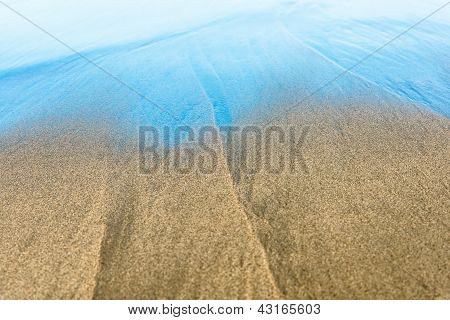 Seabed through crystal clear water at sandy beach.