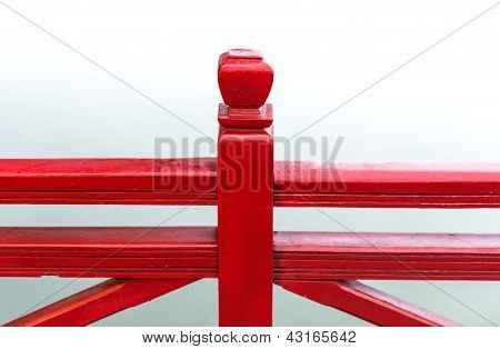 Detail of wooden red bridge with water background.