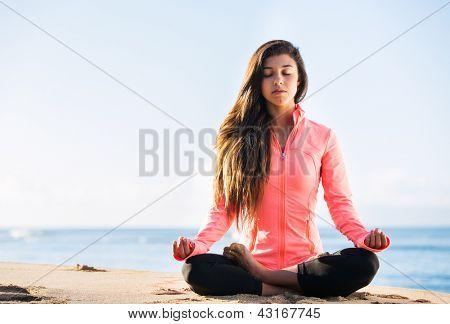 Joven, práctica de la meditación de la mañana en la naturaleza en la playa