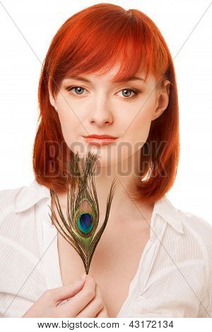 beautiful redhead woman with peacock feather over white background