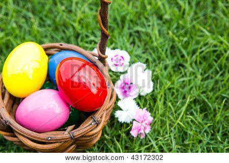 Basket of easter eggs on green grass