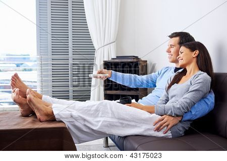 couple reaxing watching tv at home on the couch with embrace and cuddle