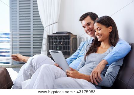 couple relaxing at home with tablet computers reading in the living room on the sofa couch.