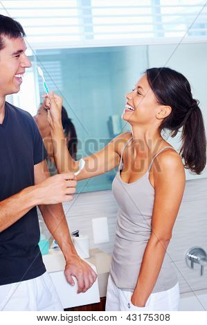 carefree real couple brushing teeth in the bathroom together. daily routine dental health