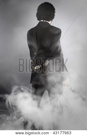 guitarist on stage full of smoke, man with black suit and guitar, back