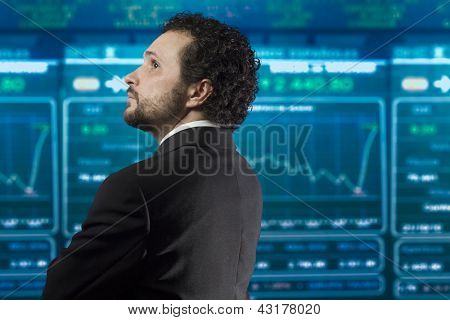 businessman with beard and black suit in the stockmarket, back