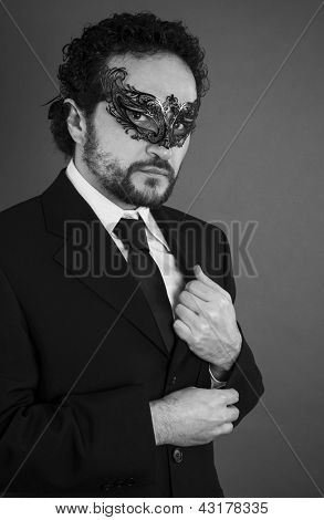 businessman with beard and black suit on artistic background, black and white