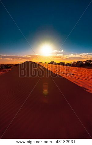 Red sand dune with ripple and blue sky
