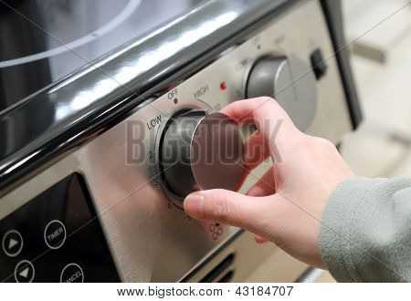 Woman turning on the oven, focus on hand turning action