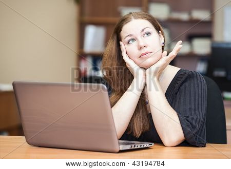Thoughtful Woman A Brunette Thinking Sitting At The Desk With Laptop In Office