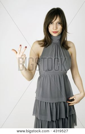 Fashion Model Showing With Her Hand The Number Three