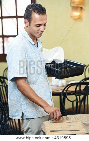 Young arab waiter man serving table with cutlery at resort hotel restaurant